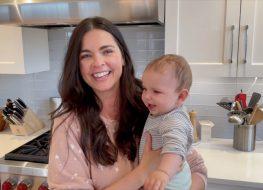 chef katie lee holding her baby daughter iris in a modern kitchen
