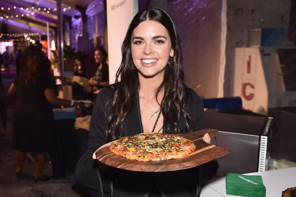 katie lee biegel holding a pan with pizza on it