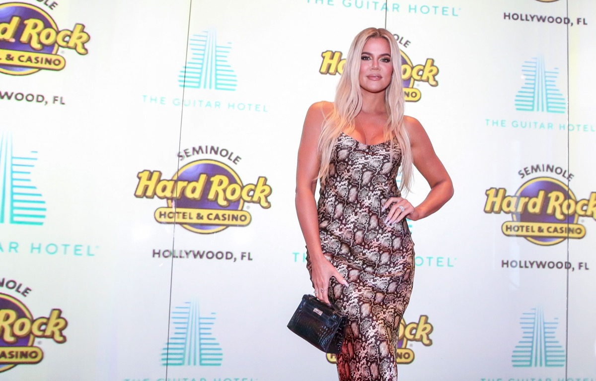 khloe kardashian in snakeskin dress in front of hard rock cafe step and repeat