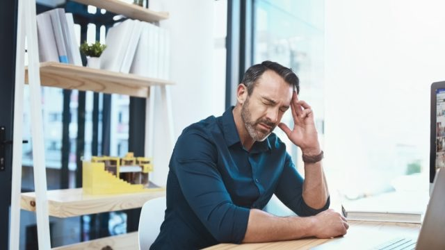 Mature businessman experiencing a headache while working at his desk