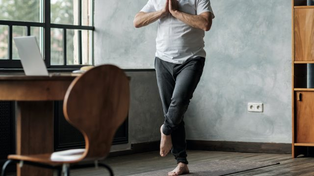 Man standing in one leg yoga balance variation. No face view. Healthy lifestyle at old age