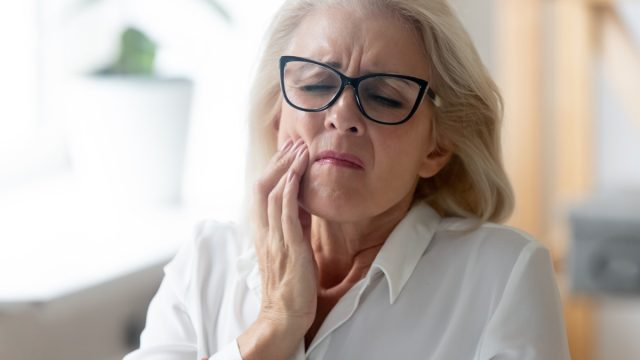 Unhappy mature woman in glasses touching her jaw.