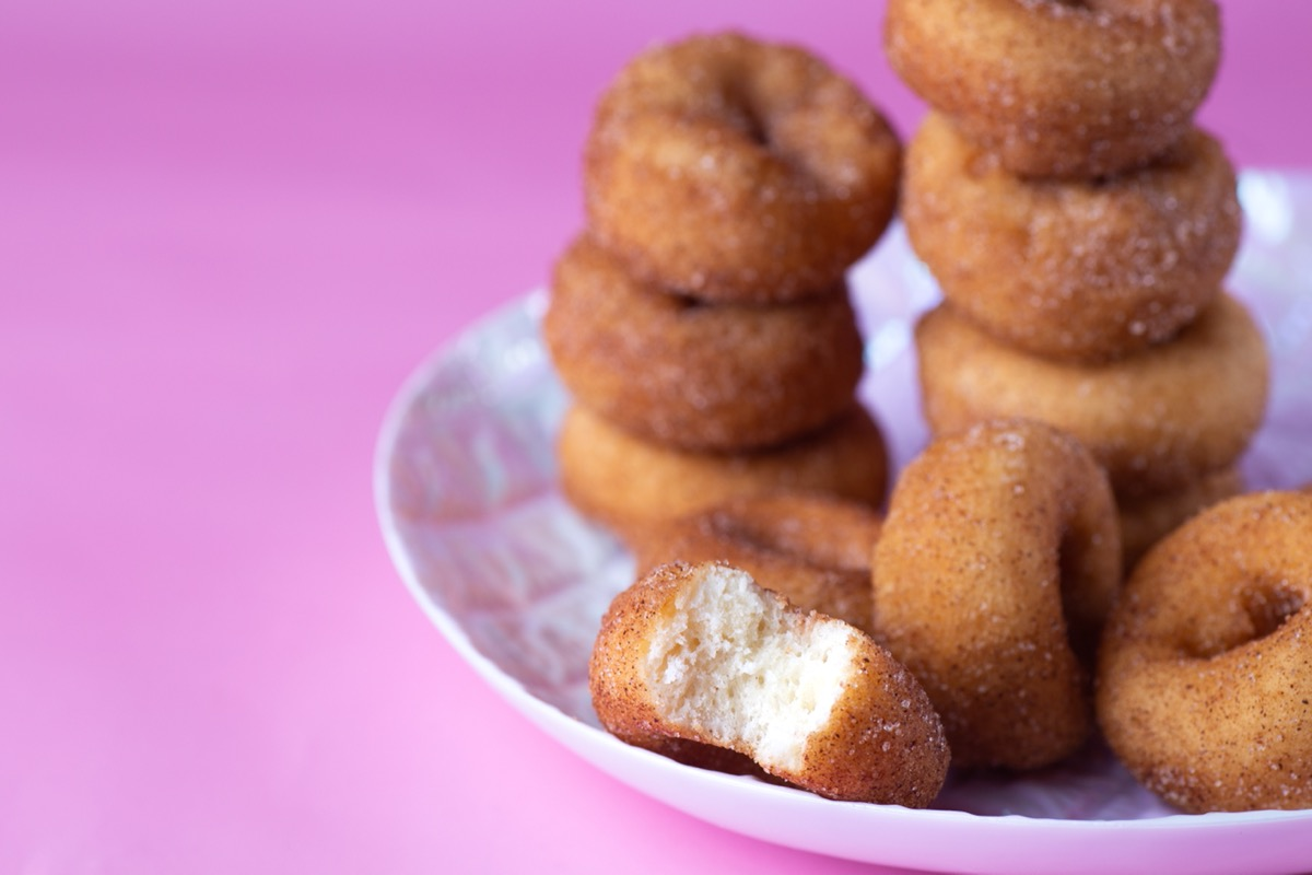 mini doughnuts on white plate with pink background