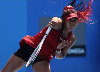 naomi osaka serving a tennis ball and holding tennis racket
