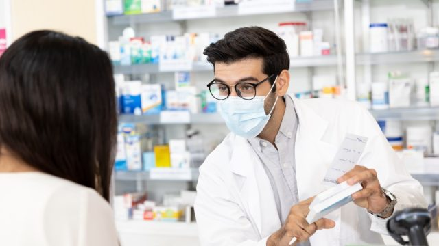 Pharmacist wearing protective hygienic mask and making drug recommendations in modern pharmacy
