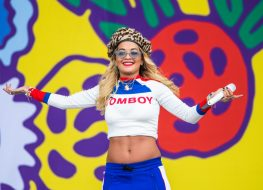 rita ora in a white crop top and blue pants on stage
