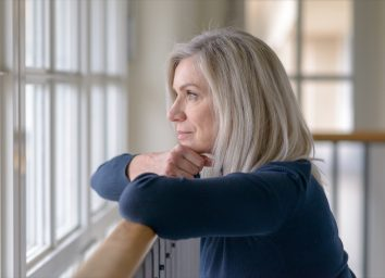 Sad blond woman watching through a window with a serious expression resting her chin on her hands as she leans on a wooden railing