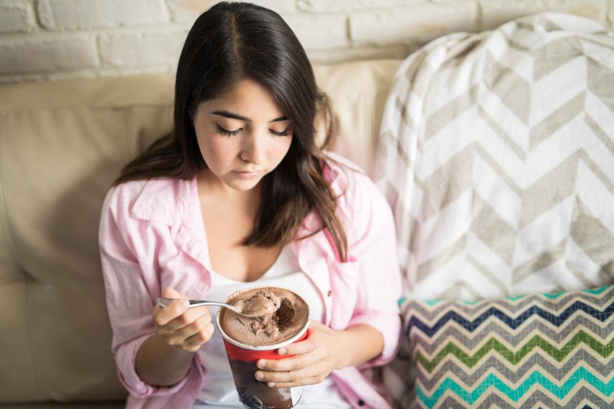sad woman eatnig ice cream in bed