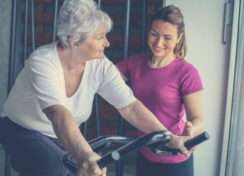 Senior woman exercising on stationary bikes in fitness class. Woman workout in gym. Senior with personal trainer.