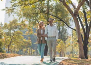 older-couple-walking-outside-in-park