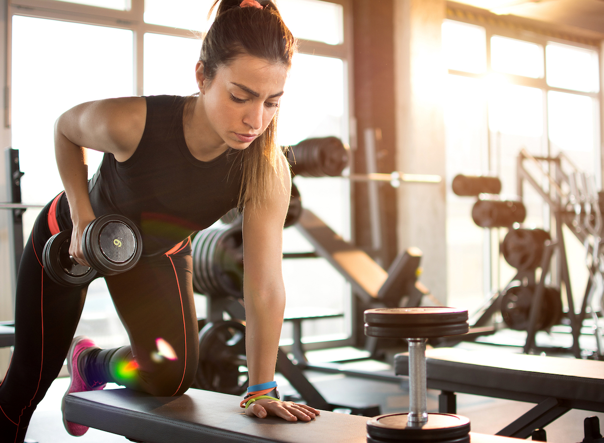 woman doing dumbell rows at gym easy morning workouts