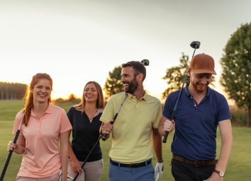 friends-walking-on-golf-course-with-clubs