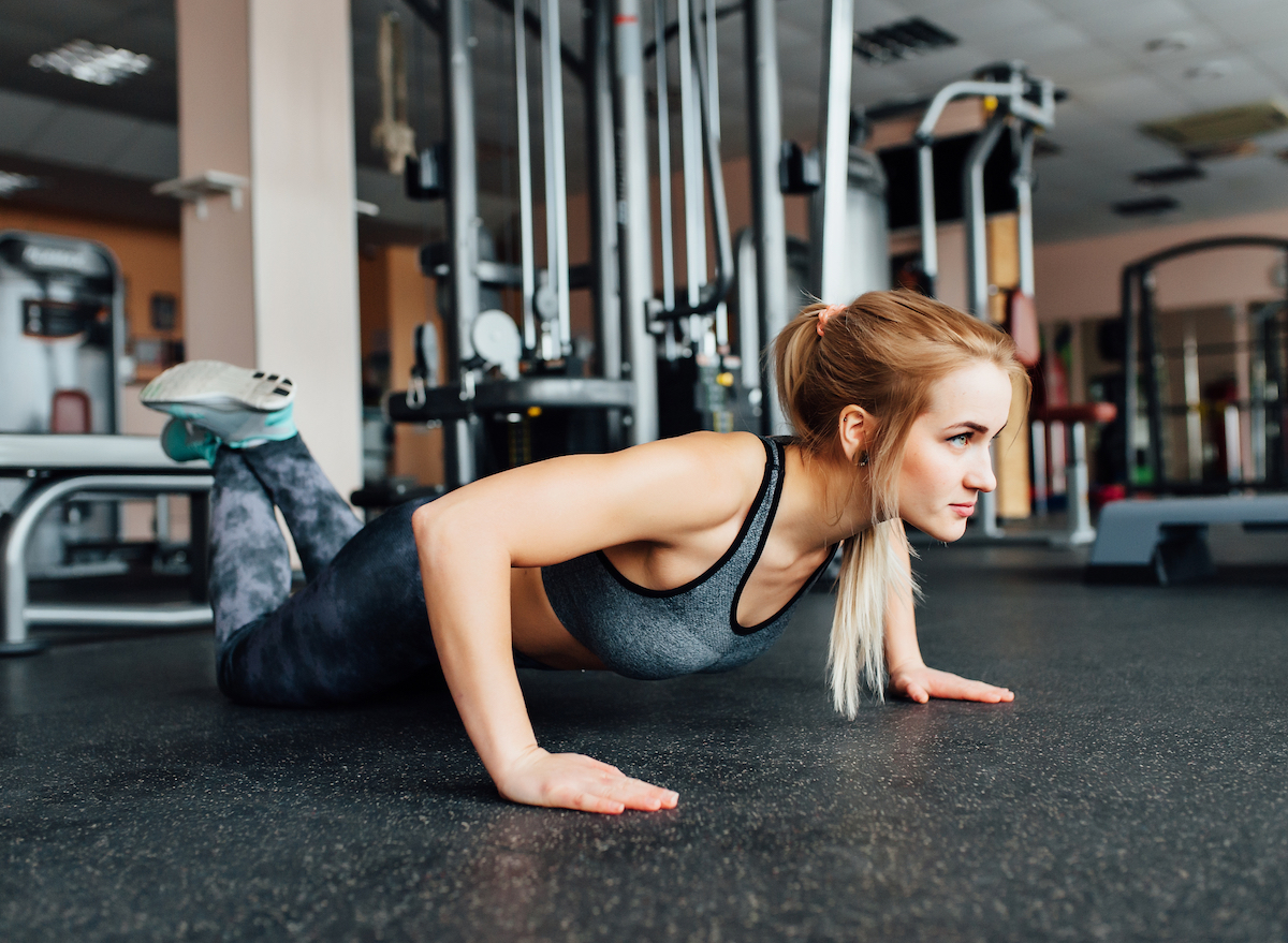 woman with long hair in gym doing a pushup from her knees