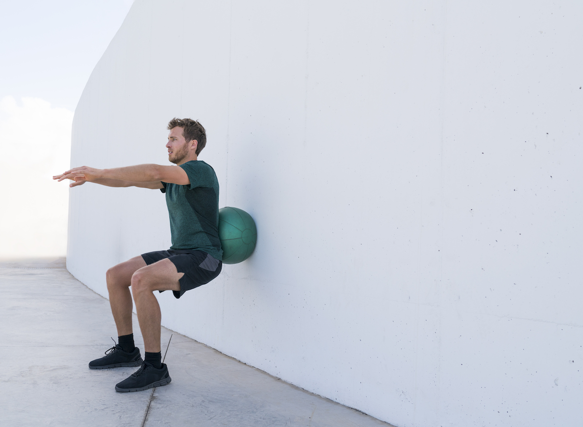 man-practicing-stability-ball-squats