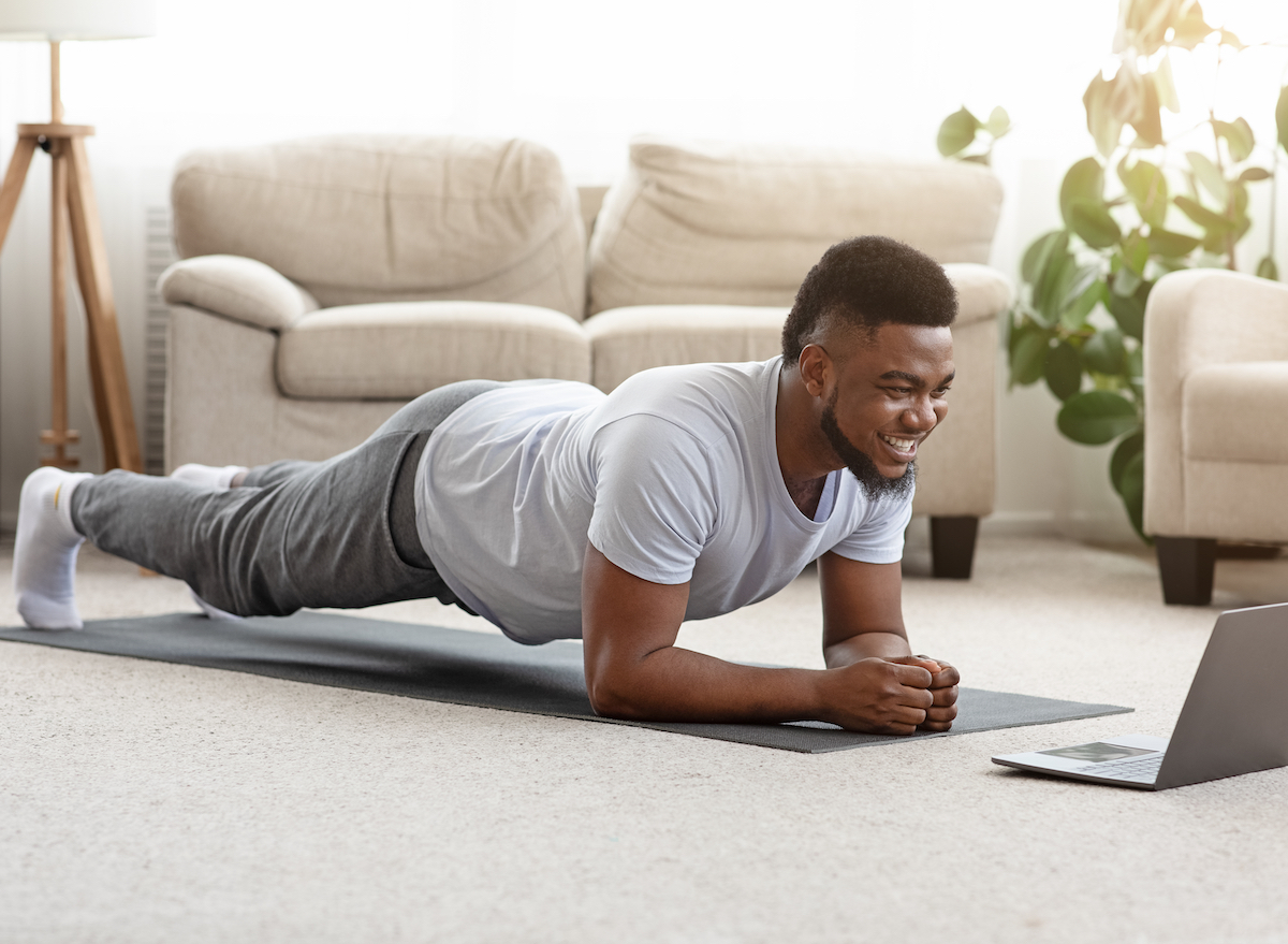 man in home doing modified plank on yoga mat in living room