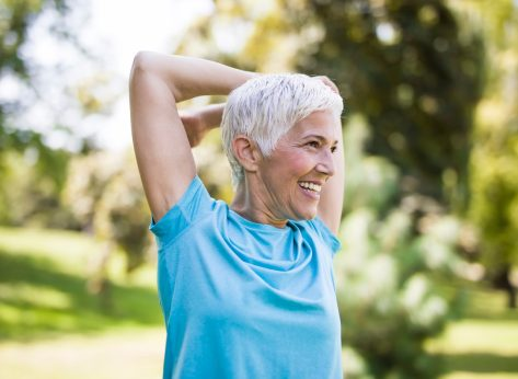 senior-woman-with-short hair-stretching-arms
