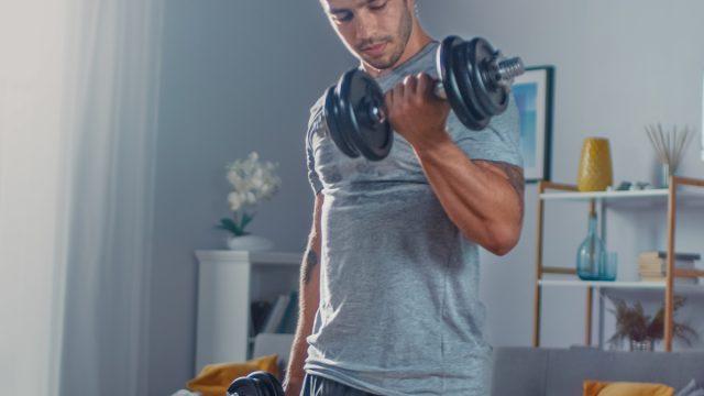 strong-man-lifting-dumbbells-living-room