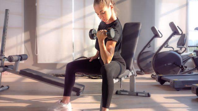 woman-lifting-dumbbells-at-gym