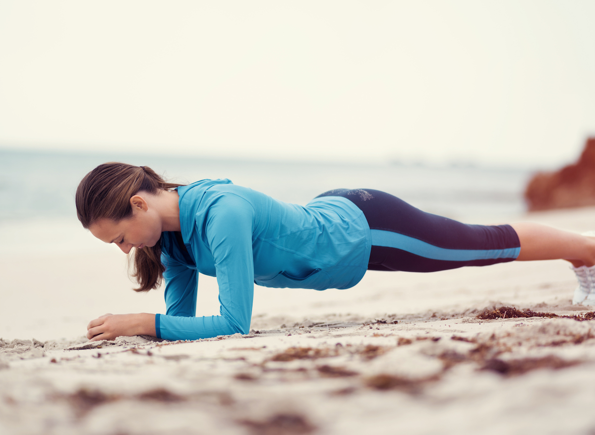 woman doing plank exercise in fitness clothes on beach