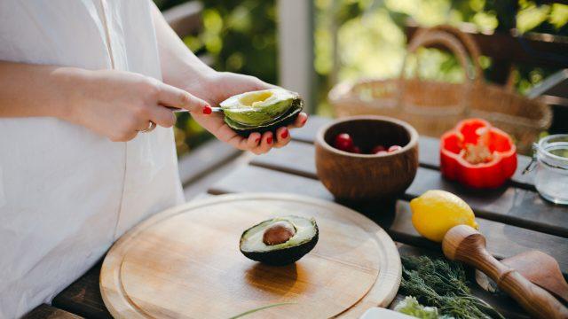 Woman's,Hands,Peeling,Avocado,For,Guacamole,With,A,Spoon.,Picnic