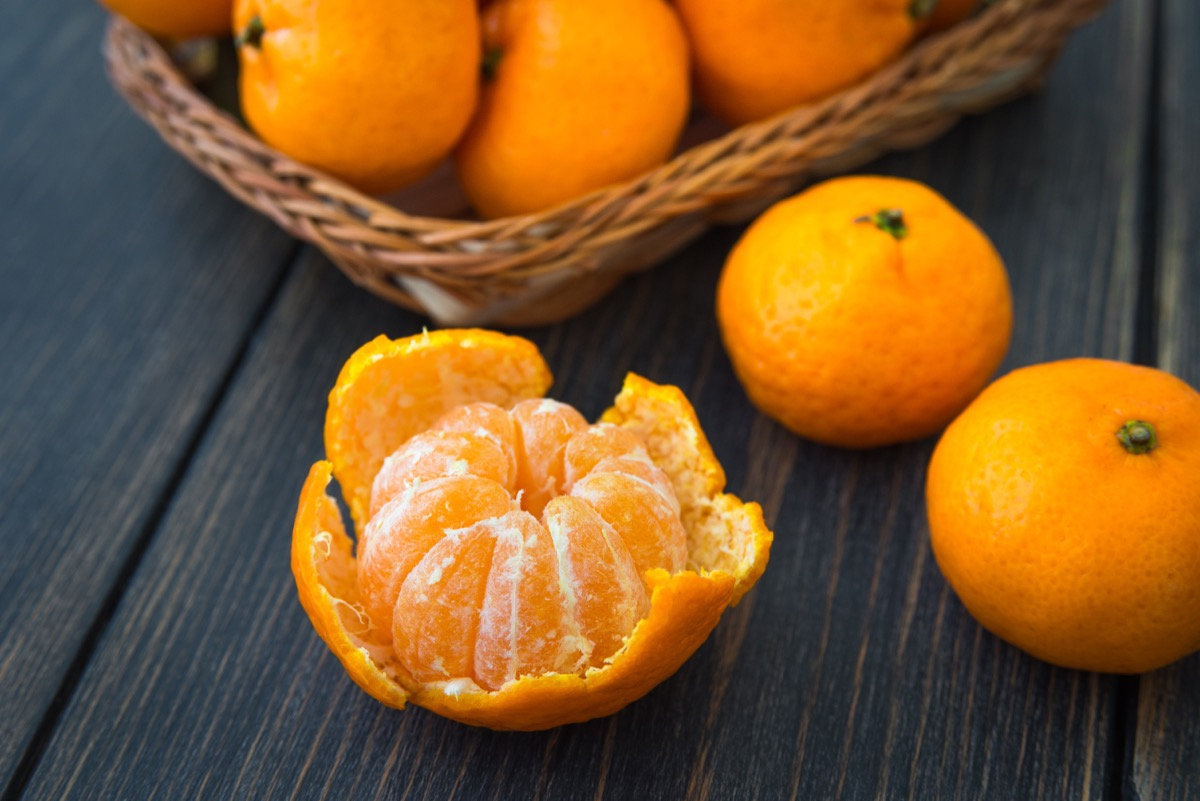 tangerines in bowl and on black background