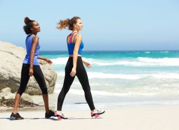 Side portrait of two young sporty women walking on the beach
