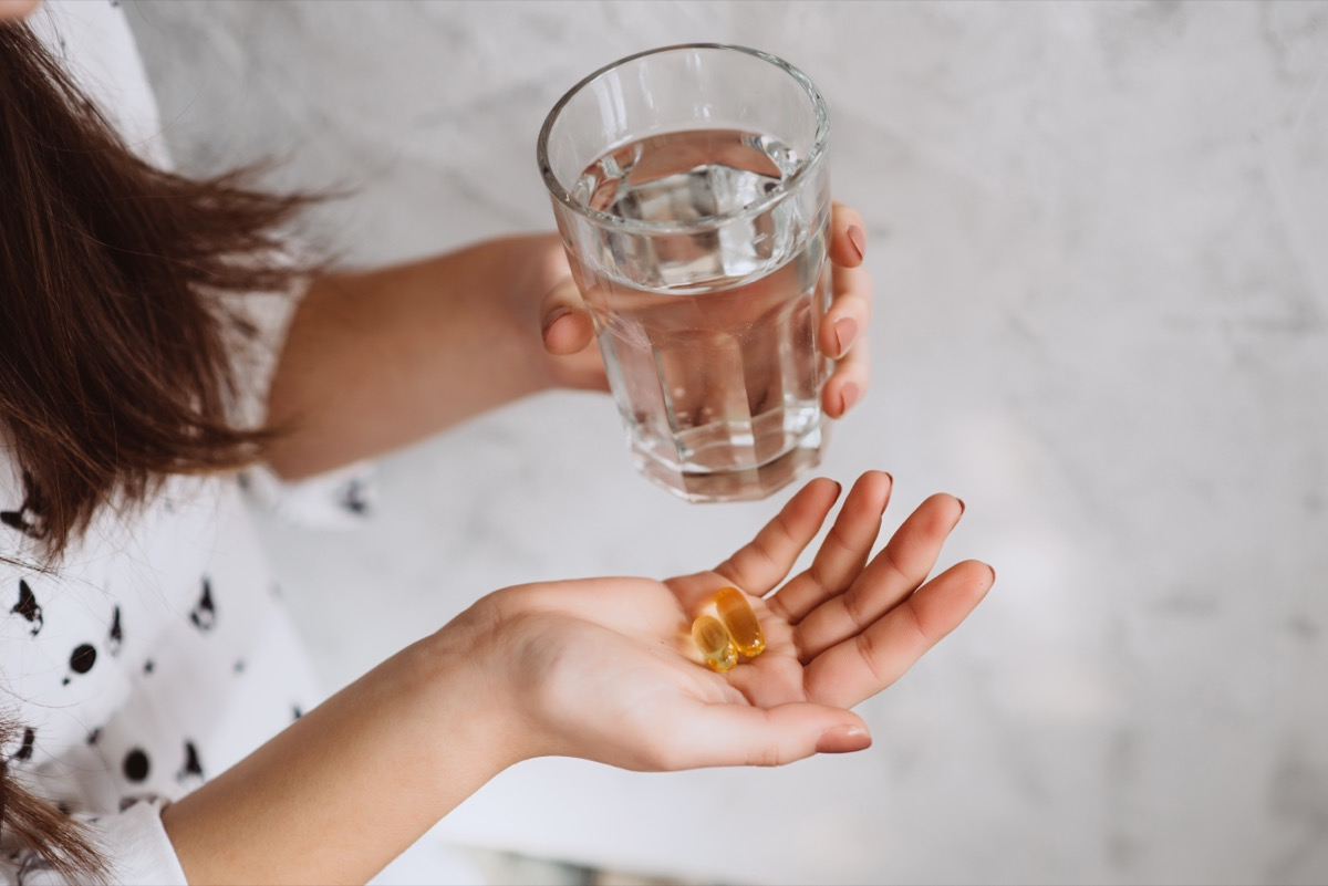 woman taking vitamin d supplement with water