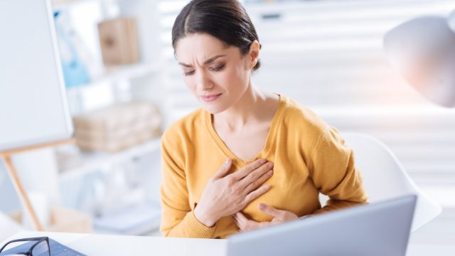 Woman touching her heart while sitting at the table in her big office.