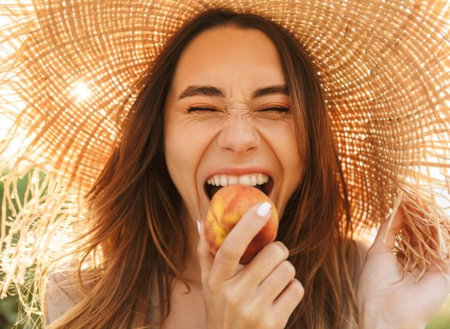 woman standing outdoors while eating a peach and wearing a straw hat