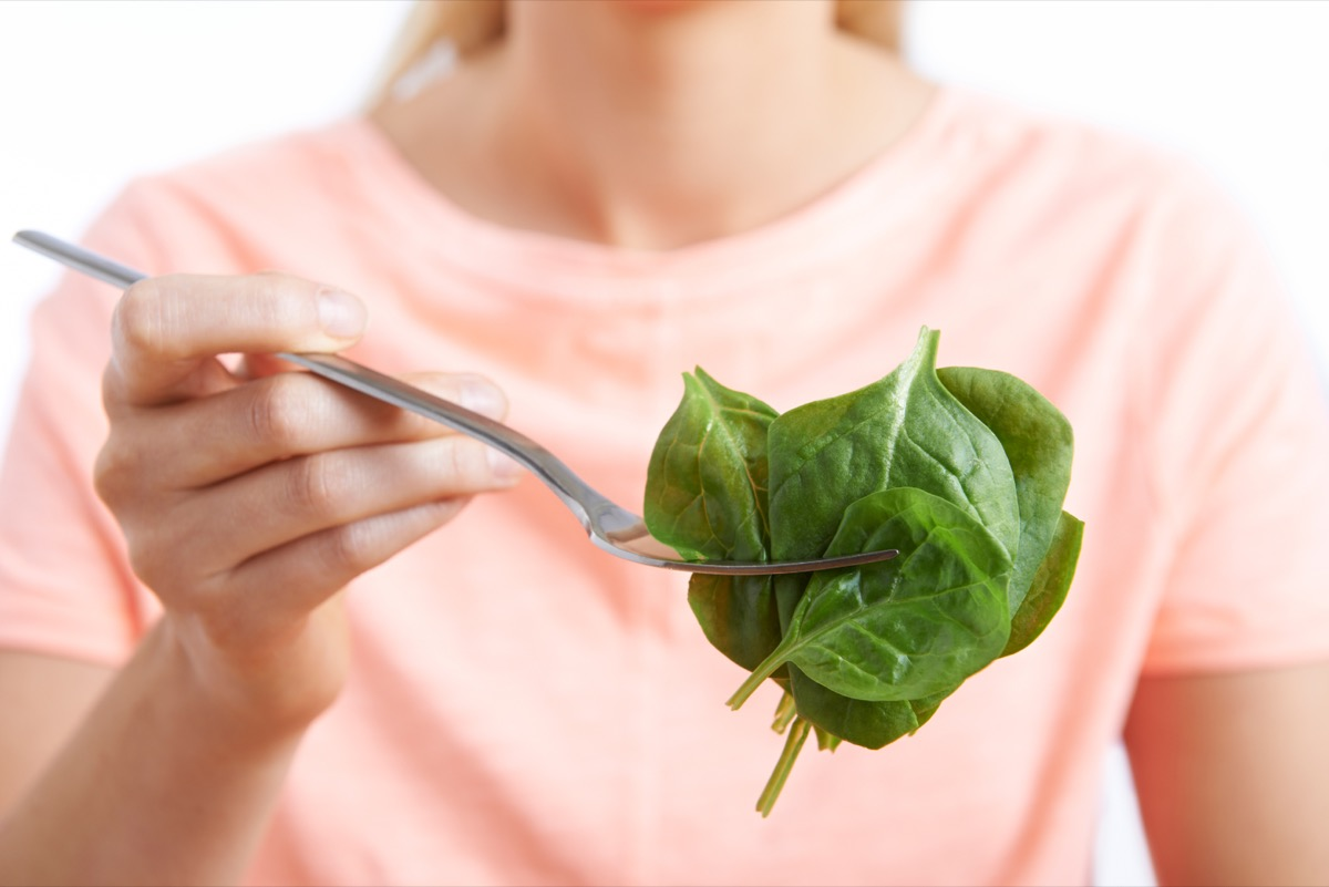 woman eating raw spinach on fork