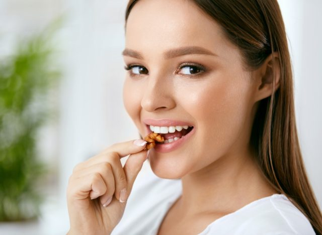 Smiling woman eating nuts.