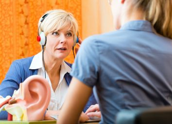 Older woman or female pensioner with a hearing problem make a hearing test and may need a hearing aid, in the foreground is a model of a human ear