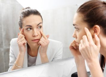 Woman checking wrinkles in front of the mirror.