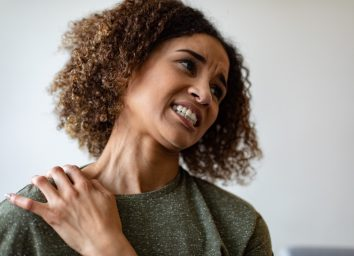 Woman experiencing neck pain.