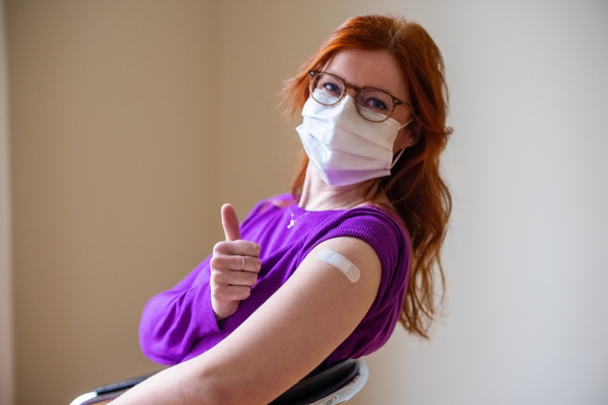 Woman wearing face mask looking at camera showing thumbs up after getting the covid-19 vaccine.