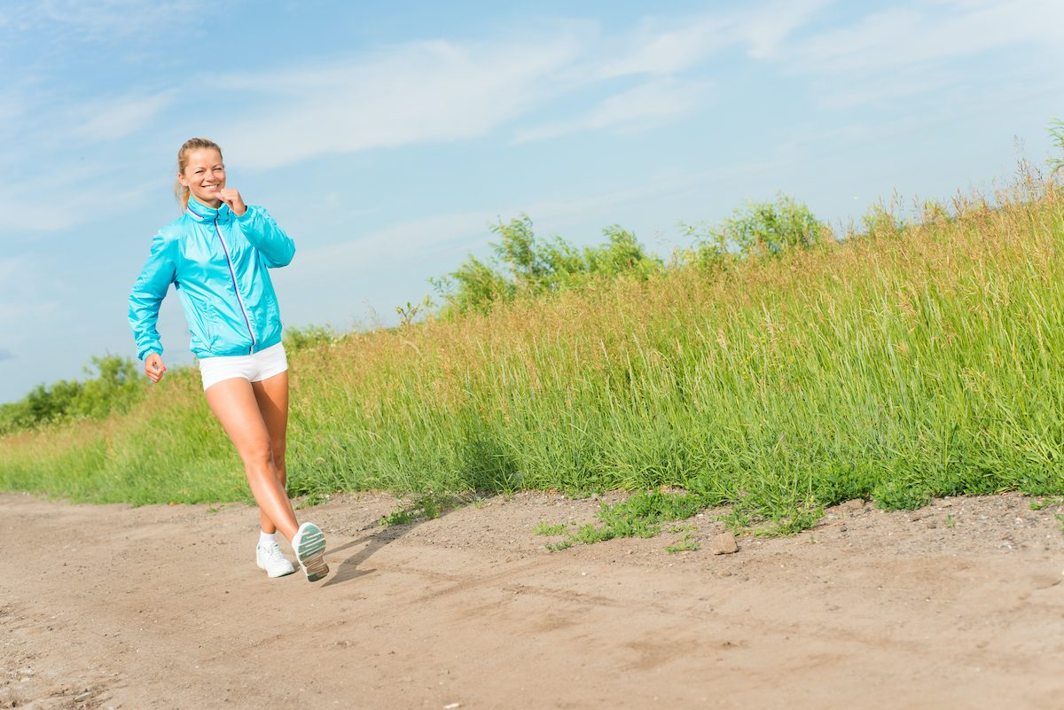 young woman running along a rural road, exercise outdoors