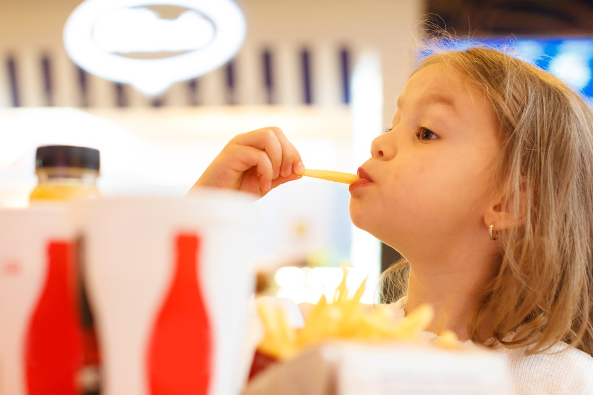 young blonde girl eating fries