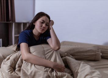 young woman sitting up in bed unable to fall asleep