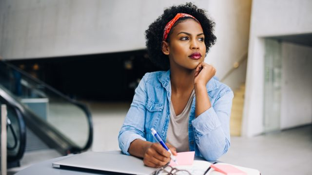 young woman daydreaming at work in a modern office building