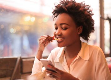 young woman looking at phone and eating fries