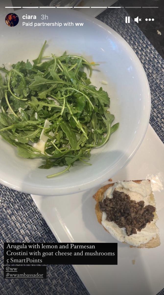 arugula salad and a mushroom crostini on white plates in instagram screenshot