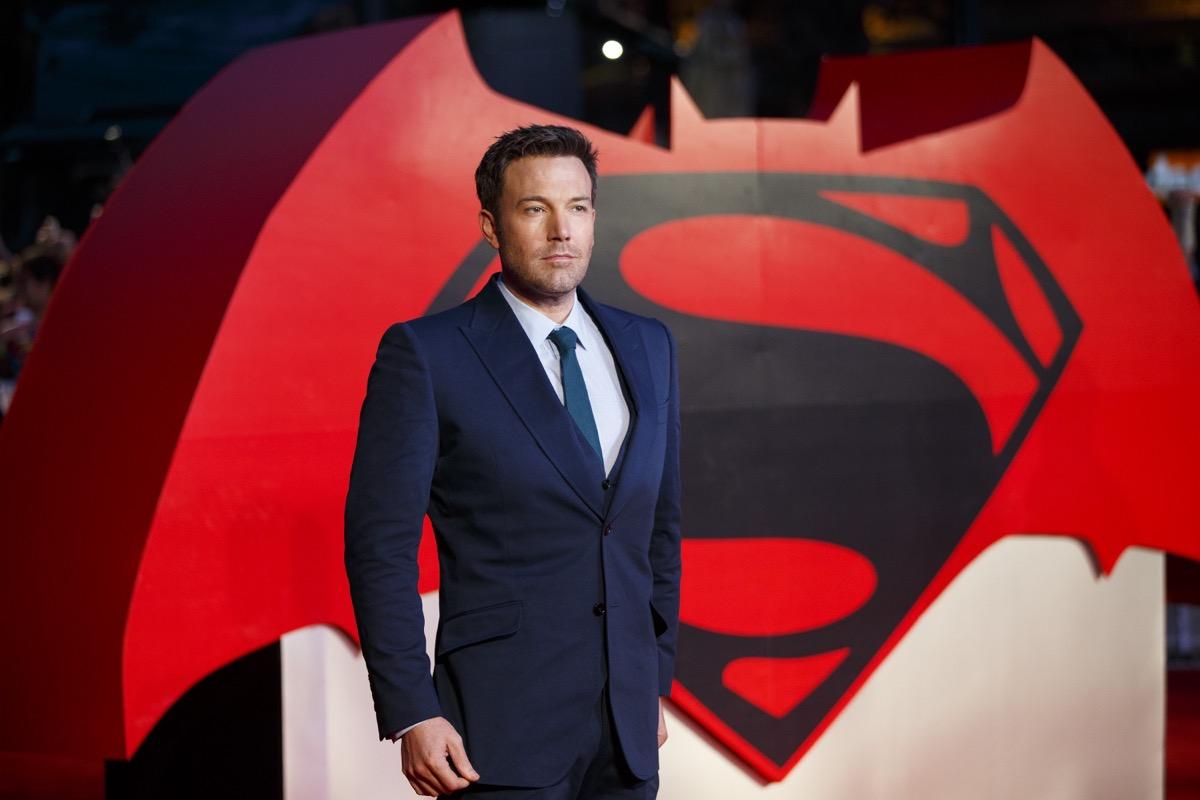 ben affleck in front of batman vs superman sign in blue suit