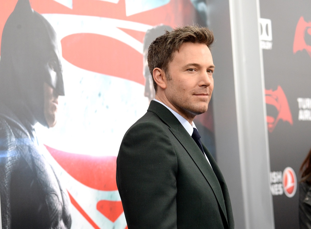 ben affleck in a black suit smiling on the red carpet