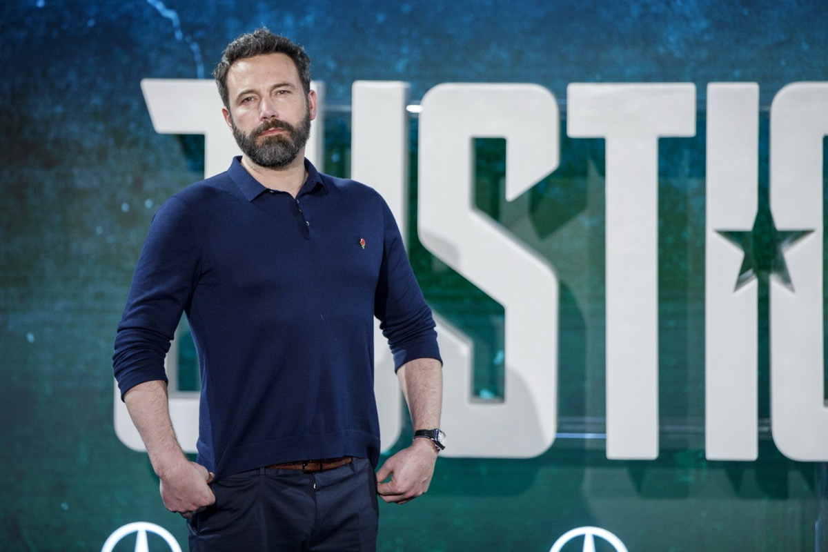 ben affleck posing in front of justice league banner