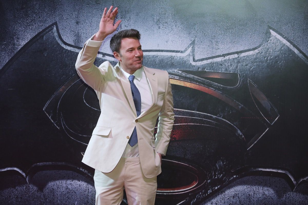 ben affleck waving in a tan suit on a red carpet