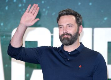 ben affleck waving on the red carpet in blue shirt