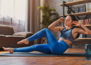 Young sporty fit woman on floor doing bicycle crunch fitness exercise at home