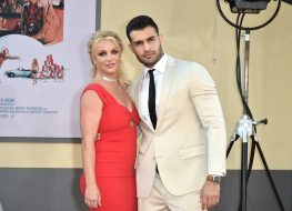 sam asghari in a tan suit standing next to britney spears in red dress on red carpet