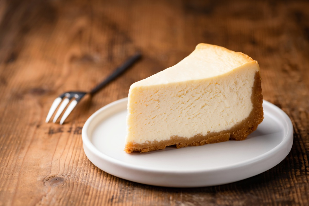 slice of cheesecake on white plate on wooden table