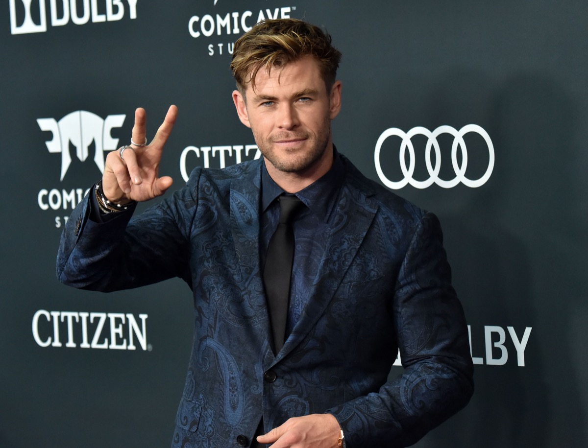chris hemsworth in blue suit giving peace sign on red carpet
